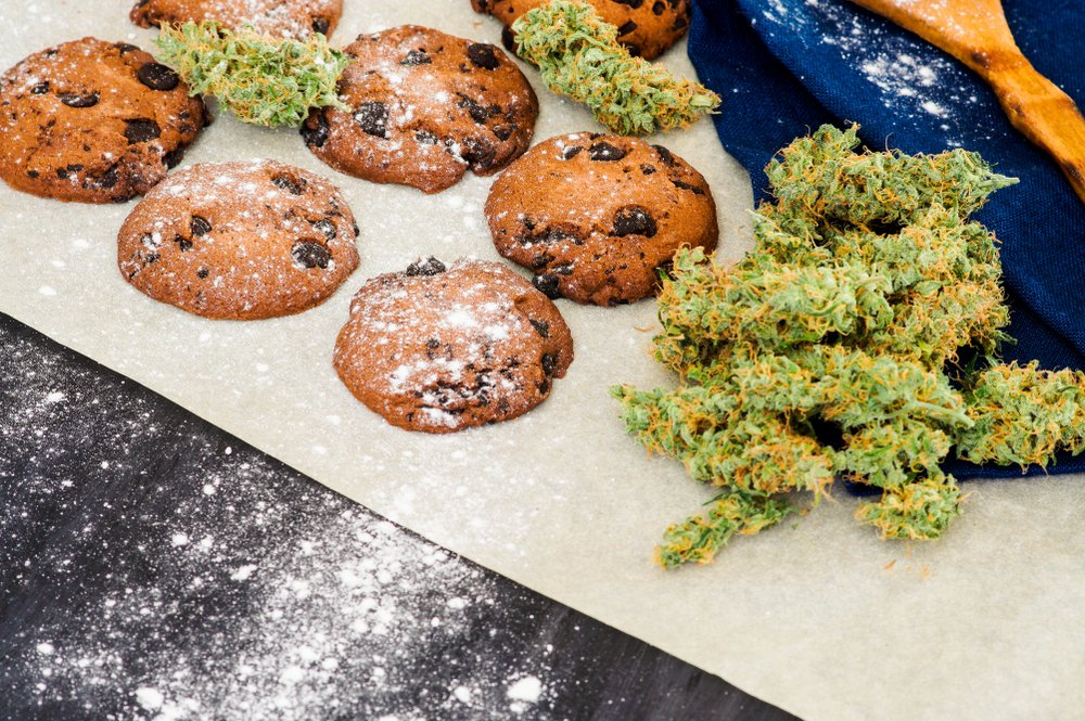 Cookies with cannabis and buds of marijuana on the table